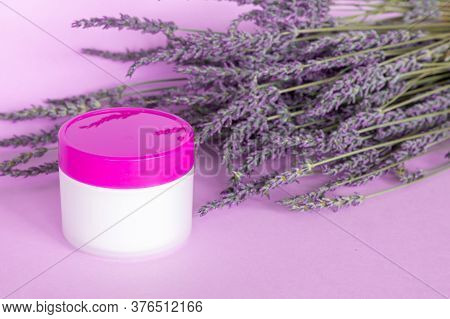 Lavender White Body Cream And Lavender Bouquet On Violet Background