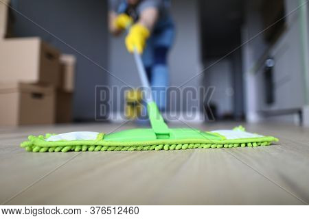 Close-up Of Professional Cleaner Washing Floor With Green Fluffy Mop. Man In Working Uniform. Handym