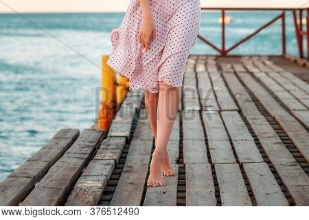 Summer Vacation. A Slim Woman In A Dress Is Walking On Tiptoe Along The Pier By The Sea. Legs Close