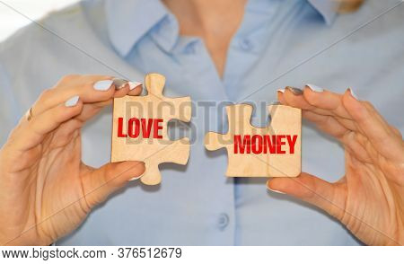 Young Woman Holding Paper Sheets With Words Love And Money On Grey Background. Marriage Of Convenien