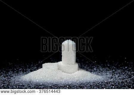 Sugar Cubes On A Black Background. Cubes Of Sugar Sprinkled With Sugar. Sugar Abuse Concept