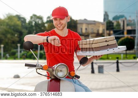 Punctual Deliverer Looking At Watches And Holding Boxes With Hot Pizza