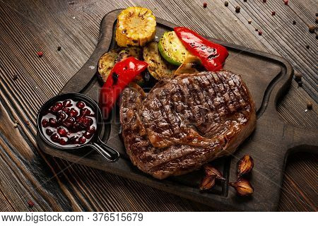 Prime Black Angus Ribeye Steak With Grilled Vegetables And Cranberry Sauce On Wooden Board