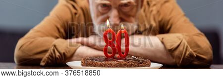 Selective Focus Of Lonely Senior Man Looking At Birthday Cake With Number Eighty, Horizontal Image