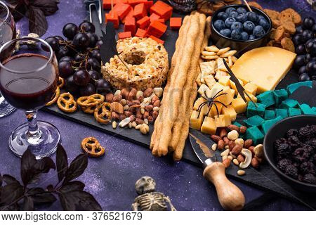 Halloween Cheeseboard With Blue And Red Cheese, Berries And Snacks.