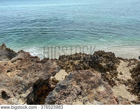 A Rocky Beach With Clear Turquoise Water In Stuart, Fl