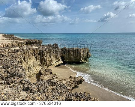 A Rocky Beach With Clear Turquoise Water In Stuart, Fl On A Sunny Day.