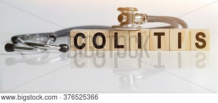 Colitis The Word On Wooden Cubes, Cubes Stand On A Reflective White Surface, On Cubes - A Stethoscop