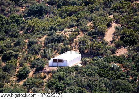 Greenhouse With Cultivated Agricultural Crops Surrounded By A Hillside Surrounded By Chaparral Shrub