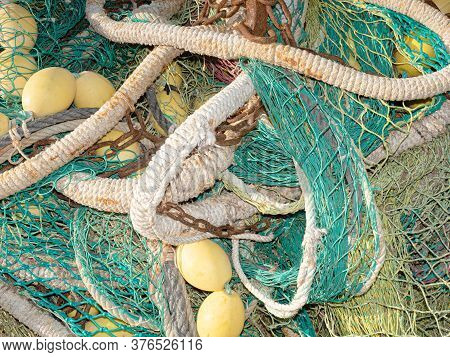 Fishing Net Is Drying In The Port. Green Net, Yellow Buoys And Rusty Chain.