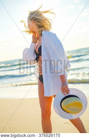 Relaxed female in bikini and shirt standing with sunhat on seashore and looking away while admiring spectacular seascape during vacation