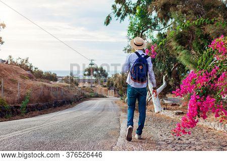 Man Traveler Walks Along Road In Akrotiri Village On Santorini Island Greece. Tourist Backpacker Adm