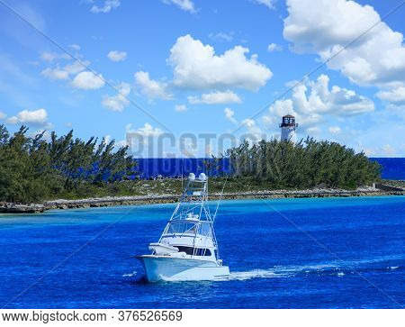 A Fishing Boat Entering A Channel By A Lighthouse In Nassau Bahamas