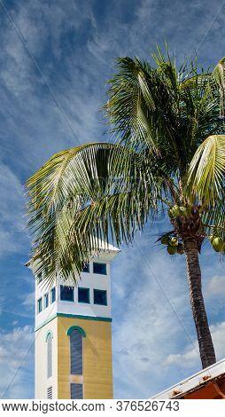 A Stucco Tower Beyond Palm Tree In Nassau Bahamas