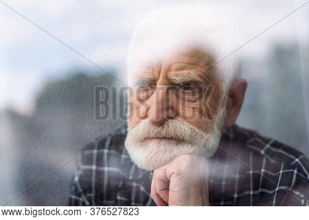 Grieving Senior Man Looking Away Through Window Glass While Holding Hand Near Chin