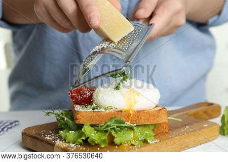 Woman Grating Cheese Onto Poached Egg Sandwich At Table, Closeup
