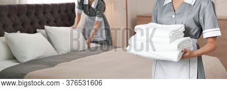 Chambermaid Holding Stack Of Fresh Towels In Hotel Room, Closeup View With Space For Text. Banner De