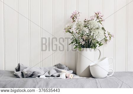 Bouquet Of Pink Soapwort And Wild Carrot Flowers In Ceramic Pitcher. Empty Coffee Cups On Linen Tabl