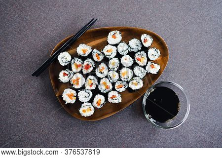 Plant-based Food, Vegan Sushi With Seaweed And Sticky Rice With Capsicum On Serving Tray Next To Bow
