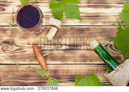 Wine Glass, Corkscrew, Corks, Wine Bottles, Grapevine On Rustic Burnt Wooden Background. Top View. C