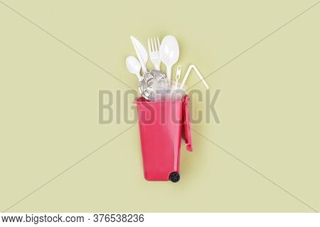 White Single Use Plastic In Garbage Container On Green Background. Concept Of Recycling Plastic. Fla