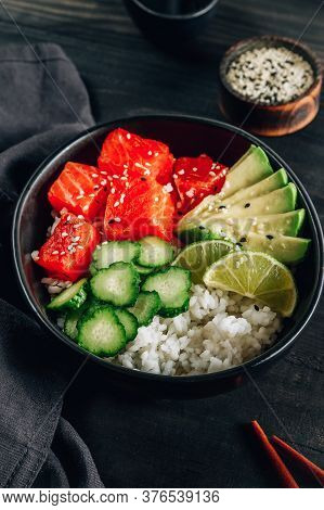 Hawaiian Salmon Poke Bowl With Cucumber, Avocado And Sesame Seeds On Black Wooden Table. Selective F