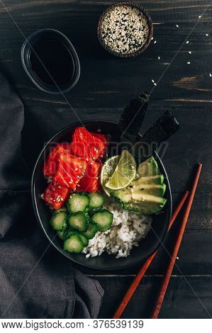 Hawaiian Salmon Poke Bowl With Seaweed, Cucumber, Avocado And Sesame Seeds On Black Wooden Table And