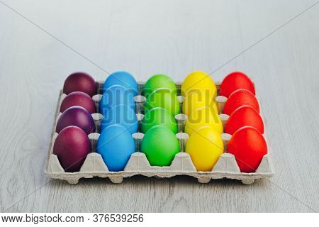 Easter festive multicolor eggs carton, light gray wooden background with copy-space