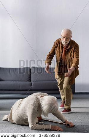 Senior Man Hurrying To Help Wife Lying On Floor Near Walking Stick