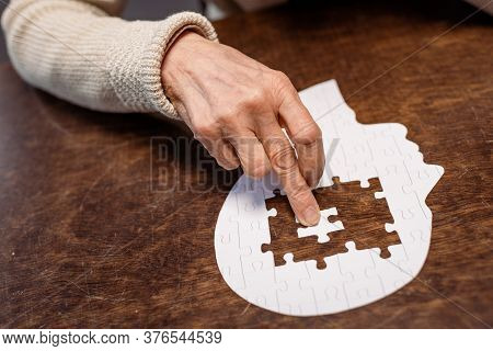Partial View Of Woman Combing Jigsaw Puzzle As Dementia Therapy