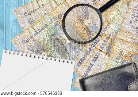 25 Egyptian Piastres Bills And Magnifying Glass With Black Purse And Notepad. Concept Of Counterfeit