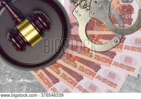 5000 Russian Rubles Bills And Judge Hammer With Police Handcuffs On Court Desk. Concept Of Judicial