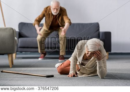 Selective Focus Of Senior Man Hurrying To Help Wife Lying On Floor Near Walking Stick