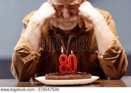 Selective Focus Of Lonely Senior Man Leaning On Hands While Looking At Birthday Cake With Number Eig