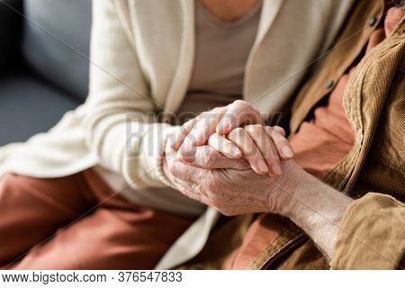 Partial View Of Senior Couple Holding Hands, Selective Focus