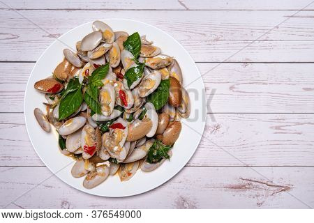 Stir Fried Clams With Roasted Chili Paste In White Dish On The White Wood Table.