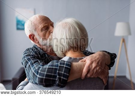 Senior Man Hugging And Kissing Wife, Suffering From Alzheimer Disease