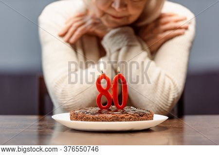 Cropped View Of Senior Woman Sitting Alone Near Bithday Cake With Number Eighty And Burning Candles
