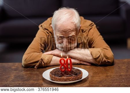 Lonely Senior Man Looking At Birthday Cake With Number Eighty