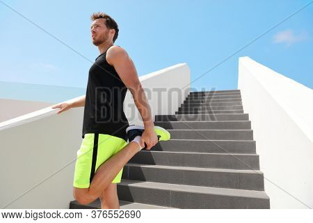 Leg muscles stretch fit man runner getting ready to run stretching legs warm-up quad stretches exercises on outdoor stairs for cardio HIIT summer workout.