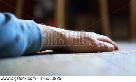 Aged Person In Blue Pullover Hand Lies On Floor Against Blurry Brown Wooden Furniture Under Bright S