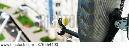Round Tv Satellite Antenna Fixed On Highrise Building Balcony Against Blurry Street And Road On Sunn