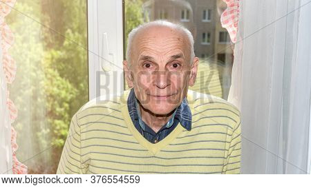 Smiling Pensioner In Yellow Pullover Stands By Plastic Window With Curtains And City Street Outside