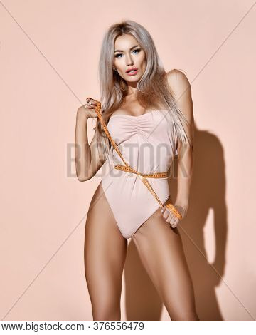 Fitness Perfect Body Weight Loss Concept. Blonde Slim Woman Measures Waist With Tape Tied It Demonst
