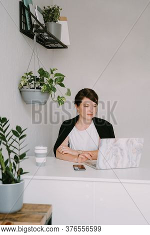 Stylish Young Woman In A White Shirt Sitting At A Table And Using Laptop At Home Or Office.