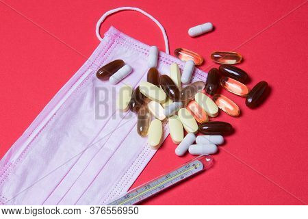 Pink Medical Face Mask, Mercury Thermometer And Tablets On Red Background. Close Up.
