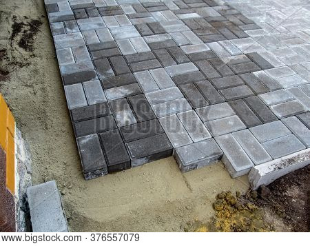 Site With Unfinished Work On Laying Gray Brick Paving Slabs. Sandy Base, Curb And Sidewalk Blocks. C