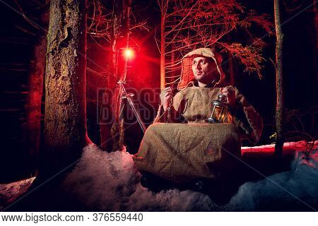 Medieval Monk In Canvas Sackcloth Robe Praying In Dark Forest With Snow And Red Light On Winter Nigh