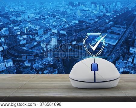 Security Shield With Check Mark Flat Icon With Wireless Computer Mouse On Wooden Table Over Modern O