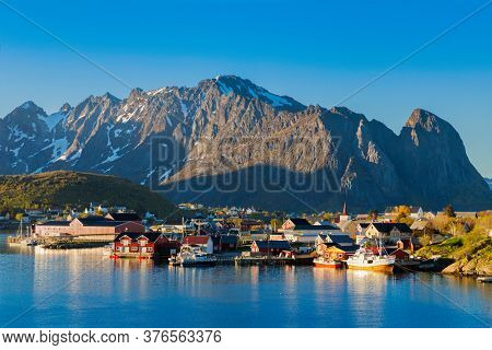 Famous Norwegian Reine The Fishing village  , Lofoten Islands,  Norway.Mountains With Snow In Background, Summer midnight sun